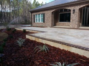 Travertine and clay brick patio on front of house by FloridaScapes